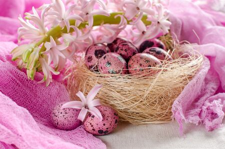 Easter egg pink color. The quail eggs. Decorative nest. The flowers of the hyacinth. Easter composition. Arrangement in pink tones. Selective focus.
