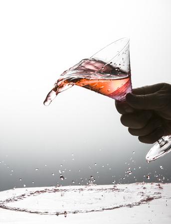 カクテルのマティーニ グラスからこぼれています。