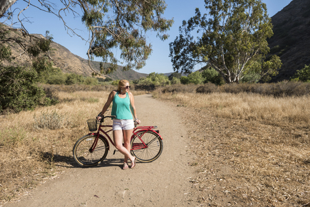 Young blond female with a beach cruiser bike on a ride outdoors