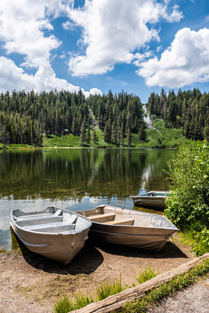 Boats docked on shore in Twin Lakes with  Twin Falls in the background in Mammoth Lakes, California