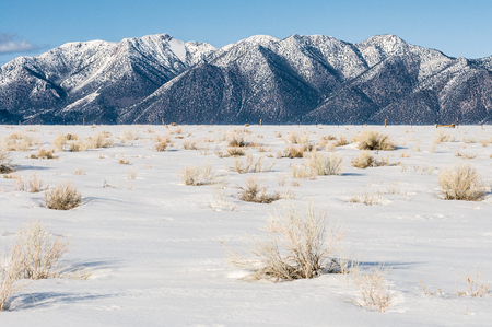 Snow covered ground with snow-capped mountains in background, California