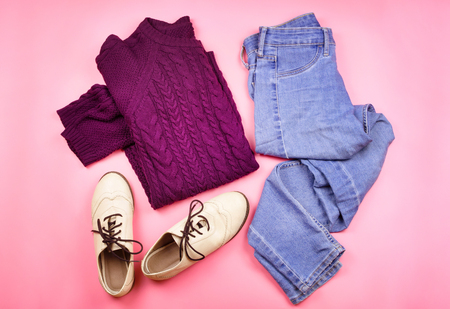 brogues: Flat lay of womans autumn cozy clothes. Pink background.