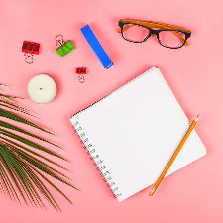 Business flatlay with glasses, palm leaf, candles, stapler, pen, notebook, colorful clipper and paper notes. Concept of a womans work place. Flat lay. Pink background. Copyspace