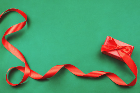 Red gift box with a ribbon on green background. Flat lay, holiday concept, toned image