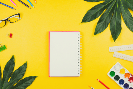 Business flatlay with tropical leaves and business and artistic accessories: colored pencils, rulers, notebook, clips, watercolors etc. Top view, yellow background. Concept of study or creative work.
