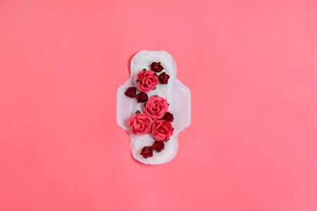 White sanitary pad with red and pink flowers on it, woman health or body positive concept. Pink background.  Flatlay. Copyspace