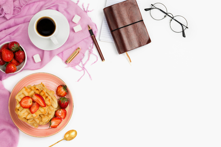 Beautiful flatlay arrangement with cup of coffee, hot waffles with cream and strawberries, glasses and other business accessories: concept of busy morning breakfast, white background. Stock Photo