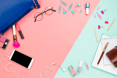 Business frame flatlay with womans blue bag, glasses, smartphone with black copyspace, cosmetics and stationary supples. Pastel pink and mint background, business mockup, women work bag contents Stock Photo