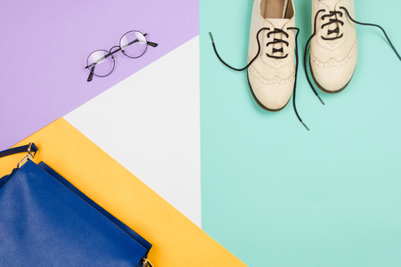 Stylish flatlay with female fashion accessories and clothes: white shoes, blue bag and glasses, blue, violet, white and yellow background. Copyspace Stock Photo
