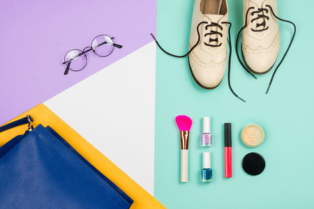 Stylish flatlay with female fashion accessories and clothes: white shoes, blue bag, glasses and cosmetics, blue, violet, white and yellow background. Copyspace Stock Photo
