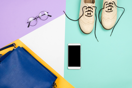 Stylish flatlay with female fashion accessories and clothes: white shoes, blue bag, glasses and smartphone with copyspace, blue, violet, white and yellow background. Copyspace
