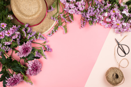 Flatlay frame arrangement with pink chrysanthemum flowers and daisies, twine, straw hat and scissors, pastel background. Copyspace