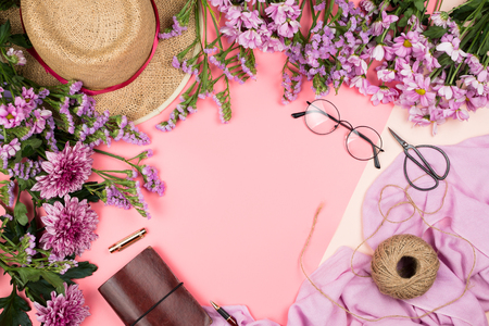 Flatlay frame arrangement with pink chrysanthemum flowers, twine, straw hat, pink scarf, glasses and notebook, pastel background. Copyspace Stock Photo