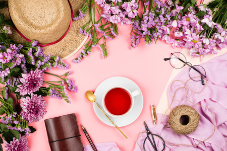 Flatlay frame arrangement with pink chrysanthemum flowers, hibiscus tea, pink scarf, glasses and notebook, pastel background. Stock Photo