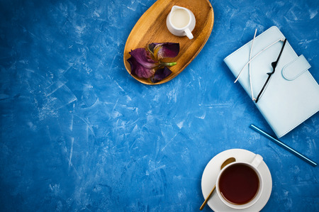 Stylish business flatlay mockup with cup of black tea, planner with glasses and pen, milk holder on wooden tray on blue cement background with copyspace