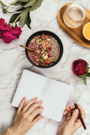 Flatlay of womans hands with notebook and smartphone, vegan smoothie bowl with chia pudding topped with granola, kiwi, pine nuts and rose buds and peon flowers on marble, healthy breakfast concept