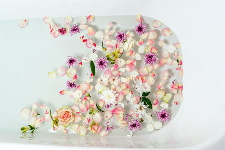 Top view of bath filled with bubble water, flowers and petals, spa or selfcare concept