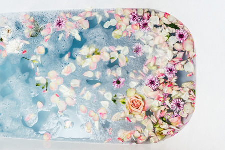 Top view of bath filled with blue bubble water, flowers and petals, spa or selfcare concept Banco de Imagens