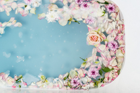 Top view of bath filled with blue bubble water, flowers and petals, spa or selfcare concept Imagens