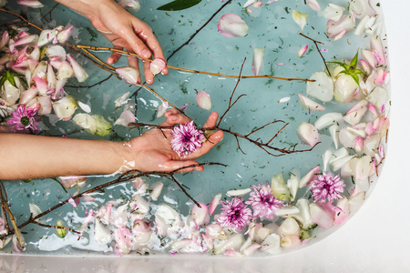 Top view of bath filled with blue bubble water, flowers, branches and petals with womans hand, spa or selfcare concept Banco de Imagens