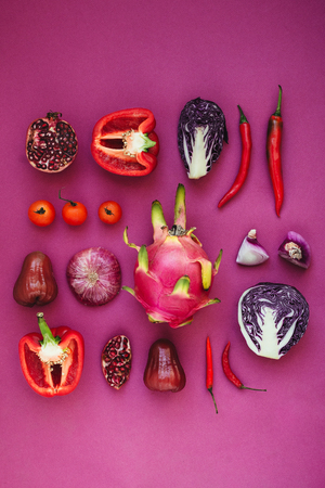 Flatlay of various red, violet and pink fruits and vegetables knolled together
