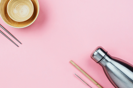 Flatlay of sustainable zero waste kitchenware: metal bottle, wooden bamboo bowls, eco straws and chopsticks on pink Imagens