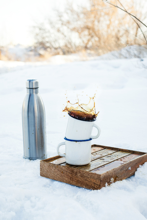 Two enamels mugs with splashing coffee or tea on wooden box outdoors and metal tumbler bottle on snow, selective focus