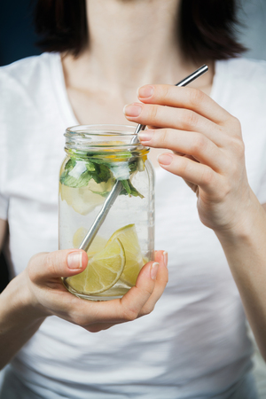 Closeup of woman's hands holding mason jar with sassy lemon and mint water, selective focus