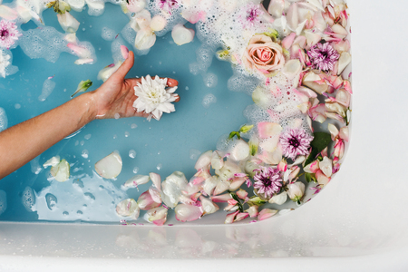 Top view of bath filled with blue bubble water and petals with womans hand holding flower, spa or selfcare concept