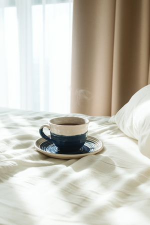 Bed with white sheets and pillow and cup of hot tea or coffee in the morning sun rays, selective focus Imagens - 124957668