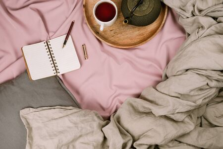 Cozy flatlay of womans bed with pink sheets and linen grey blanket with tray and notebook, selective focus Фото со стока