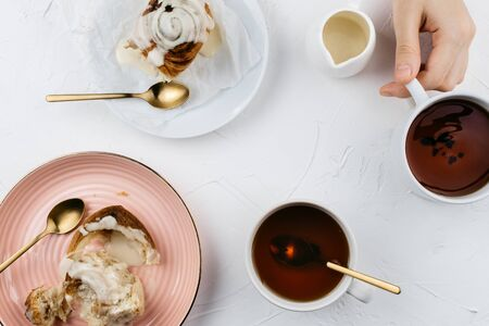 Flatlay of homemade cinnamon rolls with cream and tea on white cement background