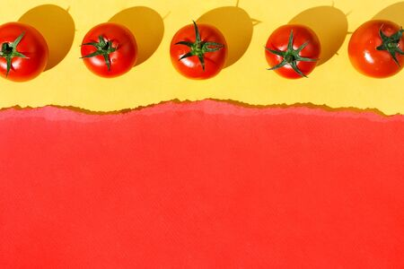 Flatlay of organic tomatoes knolled on yellow background with torn red paper, selective focus Stockfoto