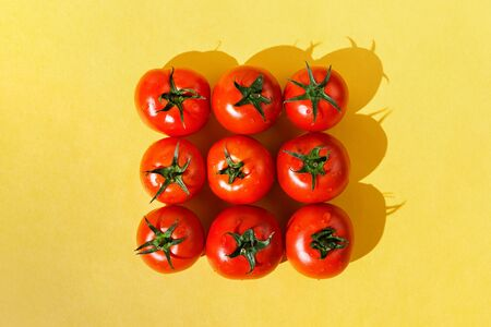 Flatlay of fresh red ripe tomatoes arranged on yellow background, selective focus Stockfoto