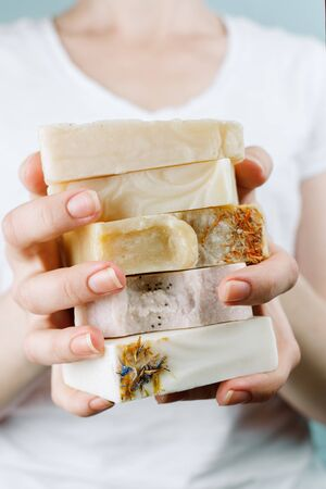 Closeup of woman's hands holding a stack of natural handmade soap, selective focus