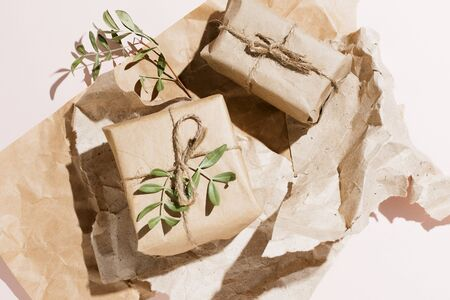 Minimalist flat lay of eco-friendly gift box wrapped in craft paper with pistachio branches Banco de Imagens