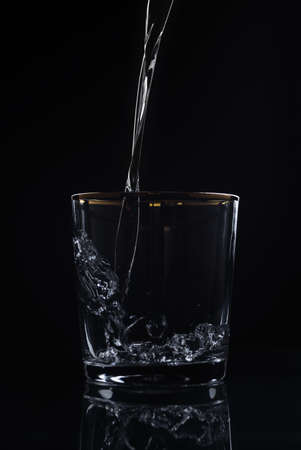 Water pouring into glass on dark background
