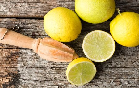 tahitian: High angle view of natural looking halved and whole tahitian limes on old wooden table with wooden citrus reamer Stock Photo
