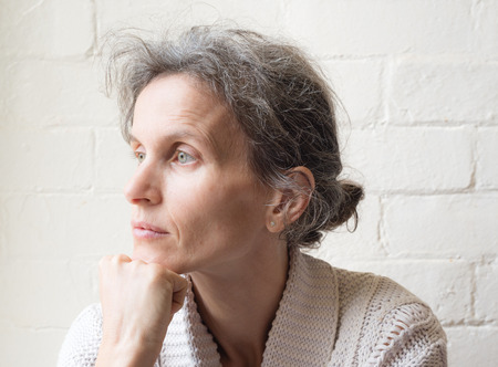 grey hair: Mature woman with grey hair resting chin on hand and looking thoughtful against white brick wall background