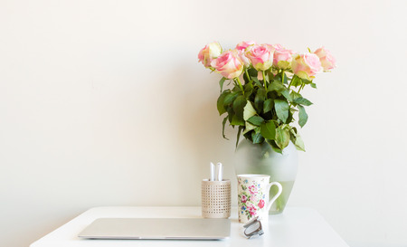 pen holder: Desk with computer, cup, glasses, pens in pen holder and vase of pink roses
