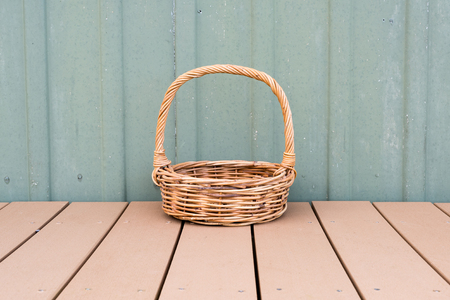 decking: Long handled wicker basket on brown decking against rustic green external wall