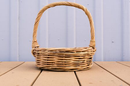 decking: Long handled wicker basket on brown decking against rustic lilac external wall Stock Photo