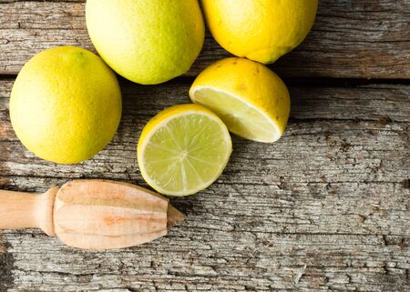 tahitian: High angle view of natural looking tahitian limes and wooden citrus reamer on old wooden table