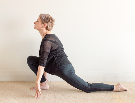 Older woman in black yoga clothing in lunge yoga posture on floor
