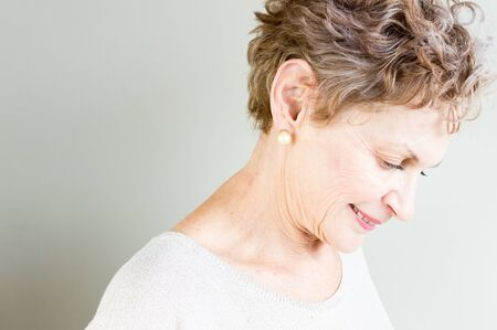 lost in thought: Profile view of older woman in beige top looking down thoughtfully