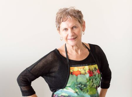 waist up: Older woman smiling in black top and colourful apron (waist up)