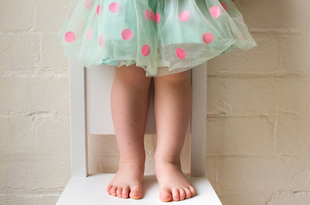 Toddler girl in green and pink polka dot skirt standing on white chair against white brick wall (cropped) Stock Photo
