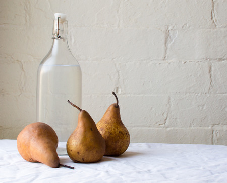Three beurre bosc pears and a glass bottle of water on a white tablecloth against a white brick wall