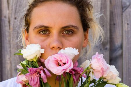 obscuring: portrait of a young woman with pink and white flowers obscuring mouth