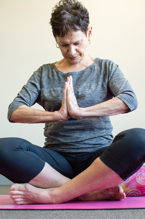yoga pants: Older woman in grey top and black pants sitting in yoga namaste position on pink mat